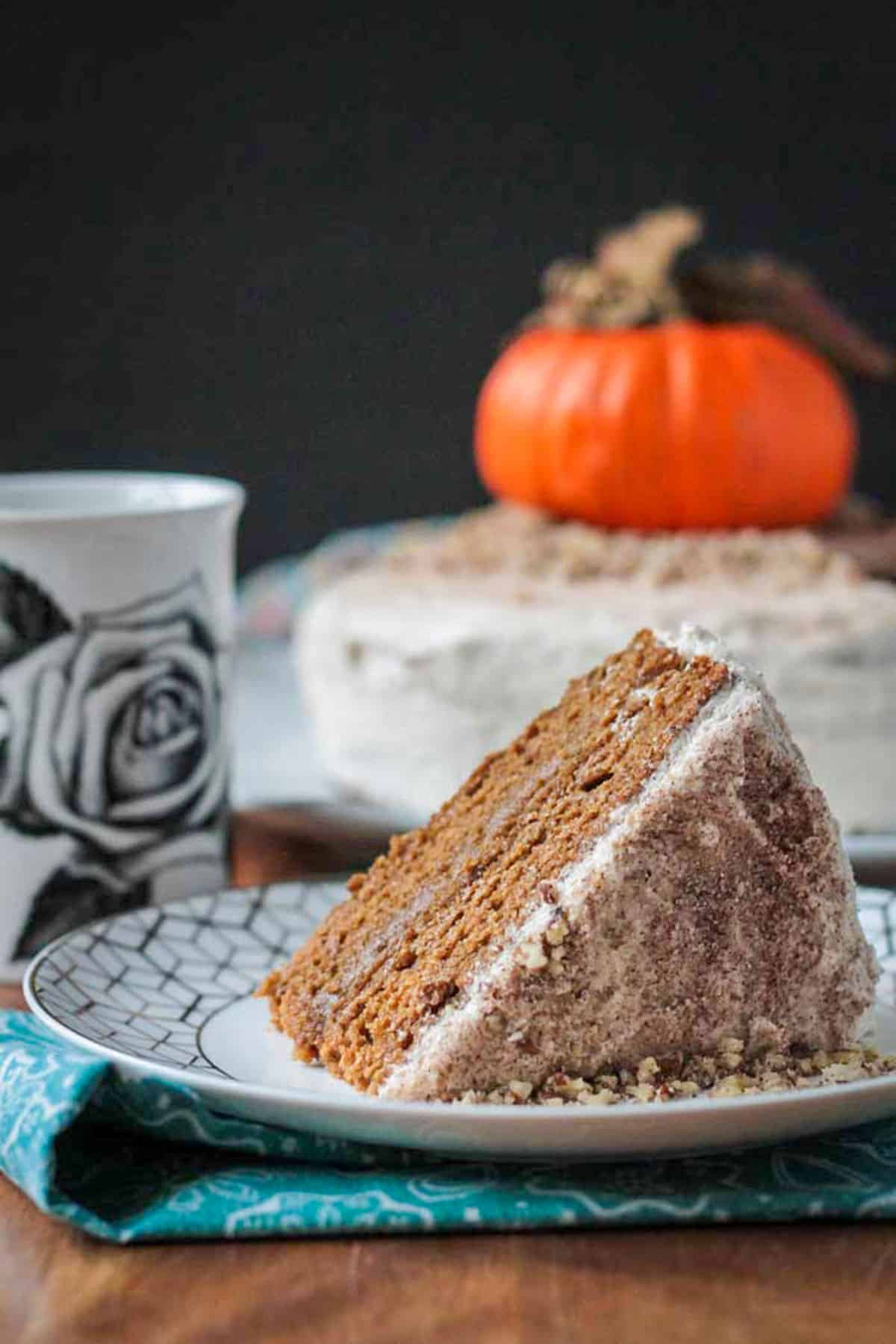 Slice of pumpkin layer cake on its side on plate with the full cake behind.