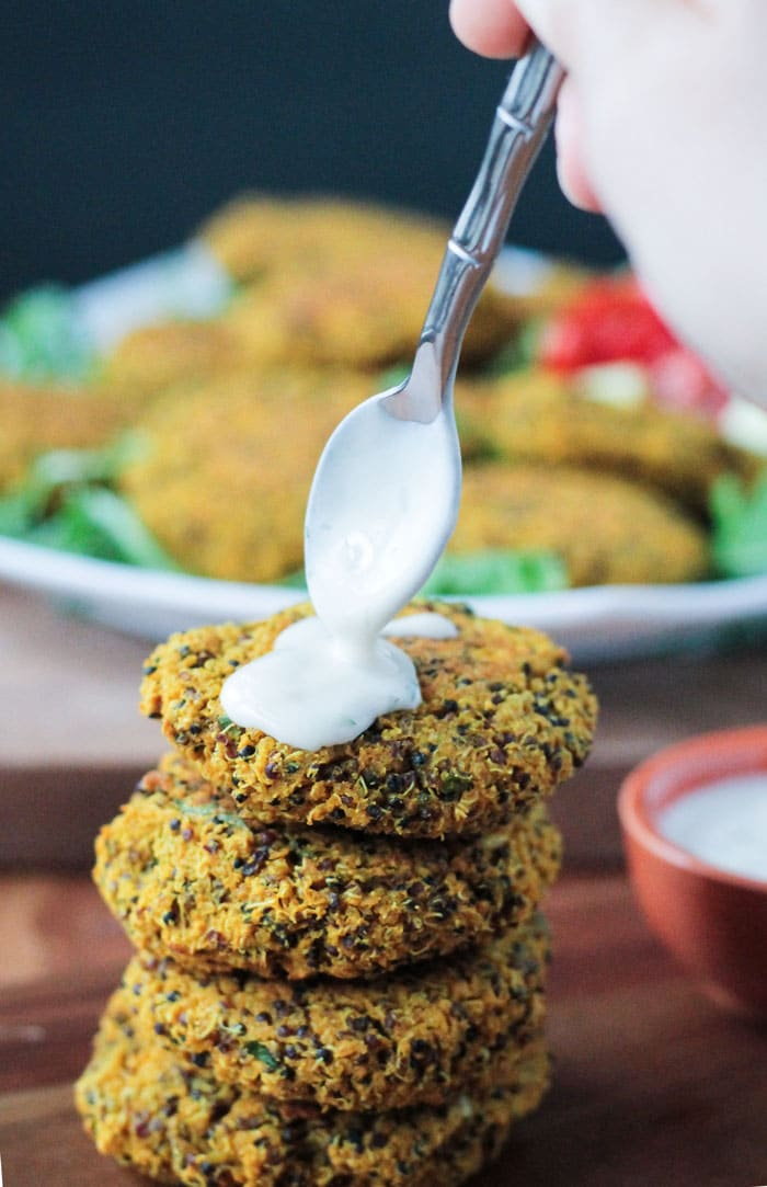 A spoon drizzling tahini yogurt sauce over a stack of four Baked Red Lentil Quinoa Fritters. Plate of fritters in the background.