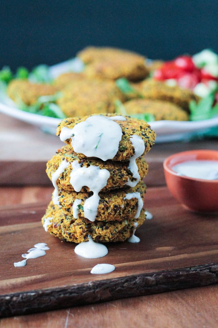 Stack of Baked Red Lentil Quinoa Fritters drizzled with yogurt sauce. Small bowl of sauce nearby.
