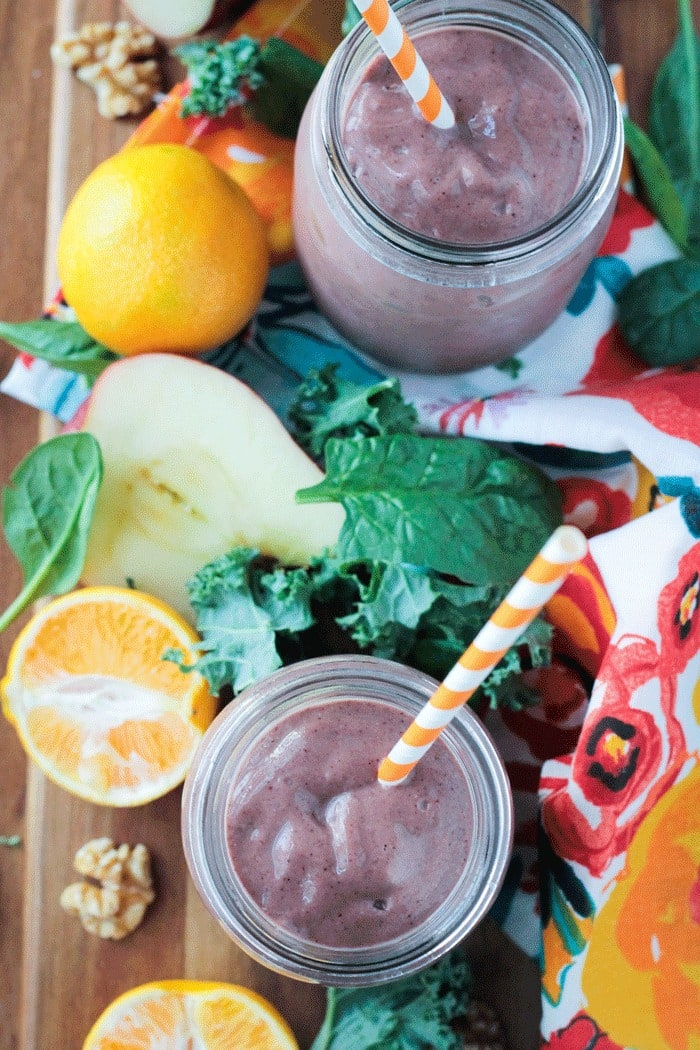 Two purple superfood smoothies in glasses with fresh fruit next to them on the table.