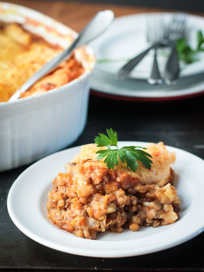 Lentil Vegetarian Cottage Pie, topped with a sprig of fresh parsley, on a white plate. Casserole dish and a stack of plates with a pile of forks on top in the background.