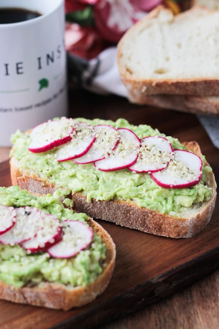 Two slices of avocado toast topped with sliced radishes and hemp seeds. Stack of bread in the background next to a mug of coffee.