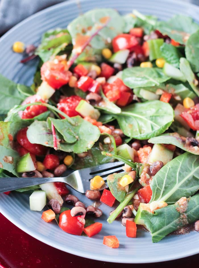 A fork stabs a bite of food from a plate of baby greens salad with black eyed peas and veggies.