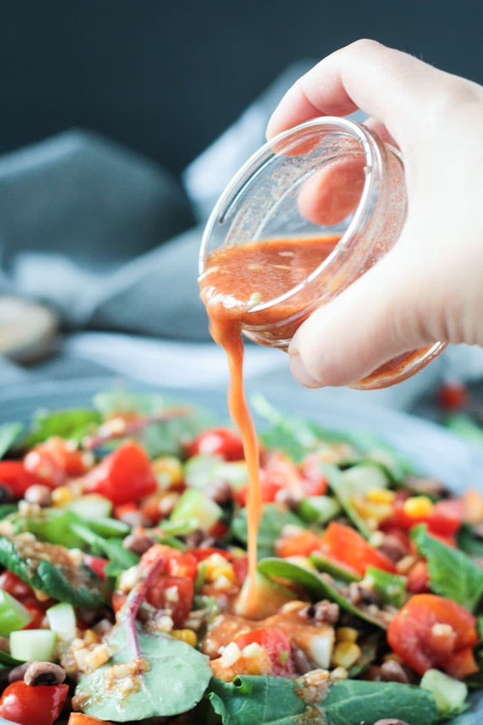 Hand pouring salad dressing from a small glass jar onto a plate of salad.