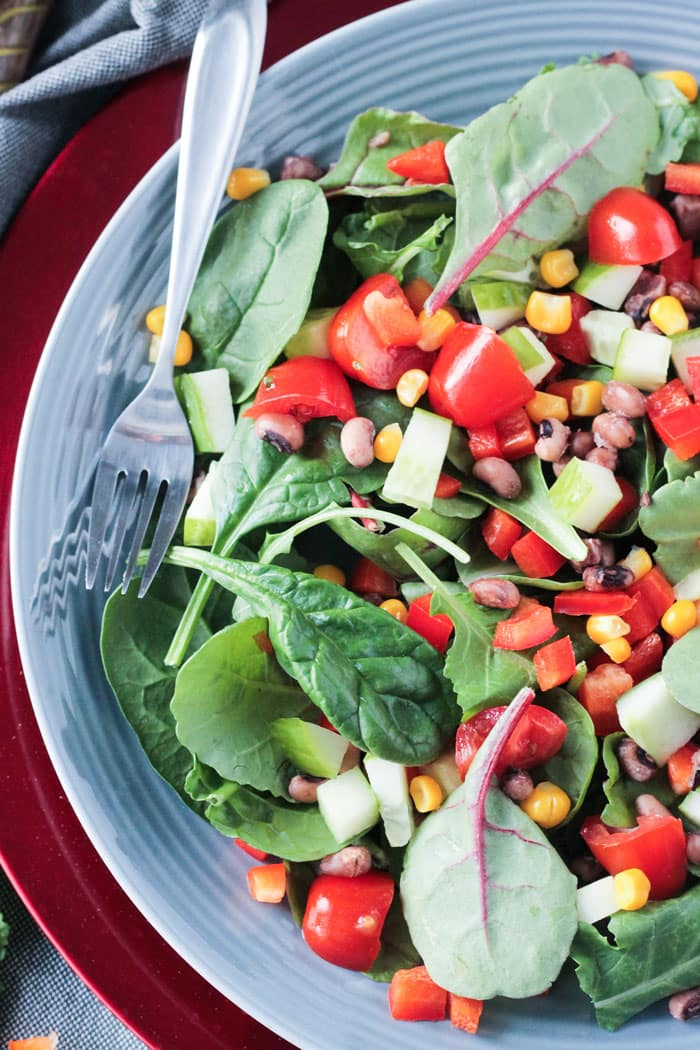 Overhead view of a salad of baby spinach, baby kale, cherry tomatoes, corn, black eyed peas, and red peppers.