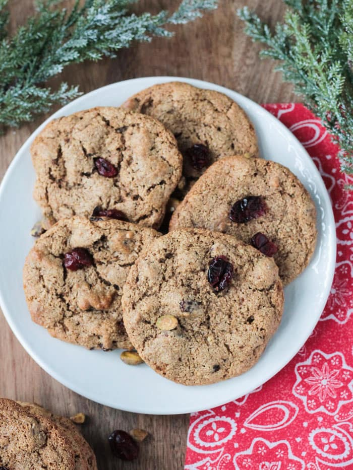 5 Cranberry Pistachio Cookies on a white plate next to a red patterned kitchen towel.