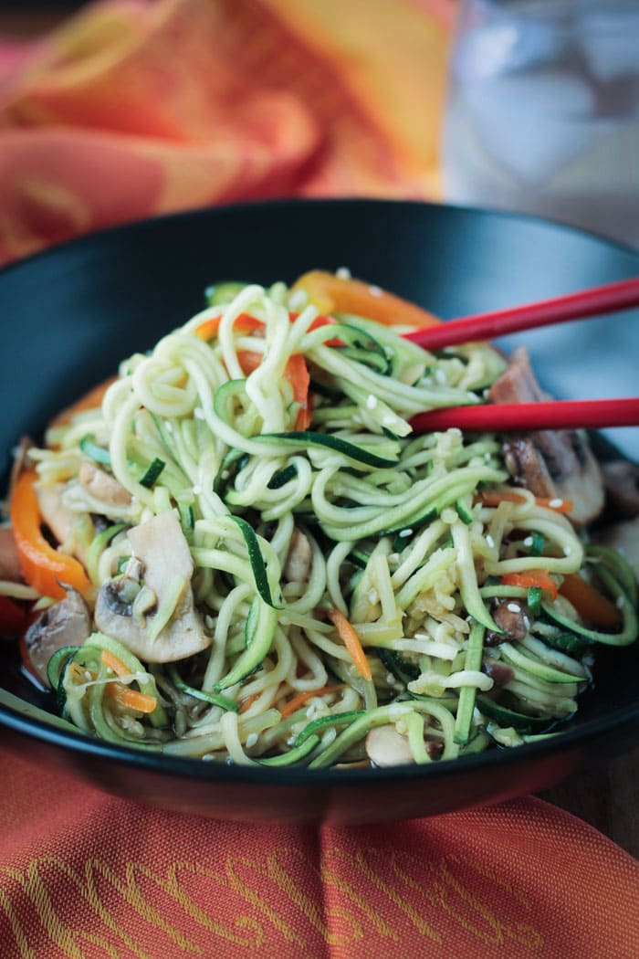 Two red chopsticks in a bowl of stir fry zucchini noodles with mushrooms and peppers.