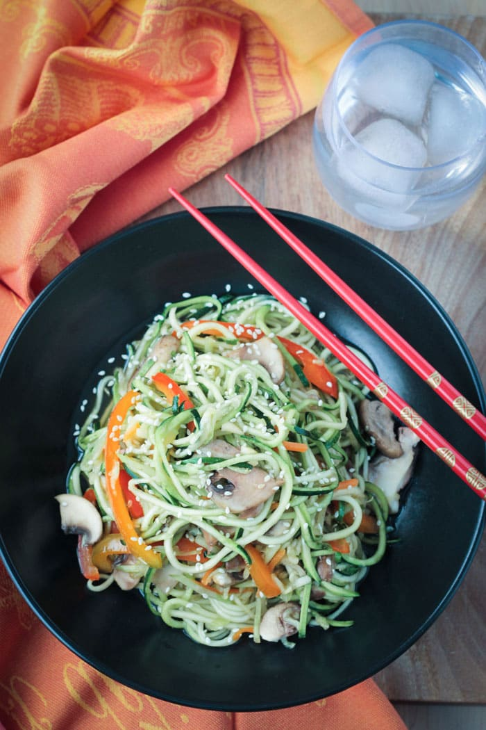 Stir Fry Zucchini Noodles in a black bowl. Two red chopsticks rest across the side of the bowl. Orange dish cloth next to the bowl and a glass of water.