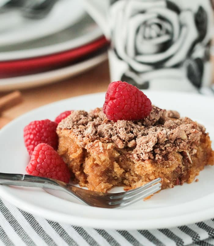 A fork rests on a plate in front of a piece of cinnamon coffee cake. Fresh raspberries on top and next to the cake.