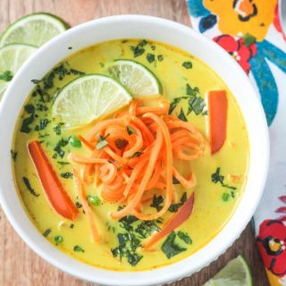 Bowl of Coconut Curry Soup with golden yellow broth, bell red peppers, spiralized sweet potato noodles, and garnished with lots of chopped cilantro and two lime wedges.