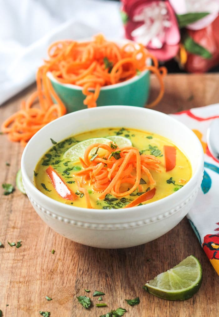 Coconut Curry Soup in a white bowl, small blue bowl filled with spiralized sweet potatoes behind. One lime slice in front of the white bowl.