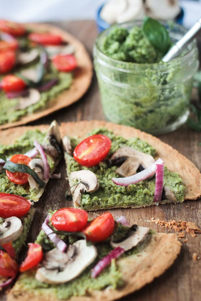 Easy Vegan Pesto Tortilla Pizza sliced into 4 slices. Small glass jar of pesto with a metal spoon in it behind.