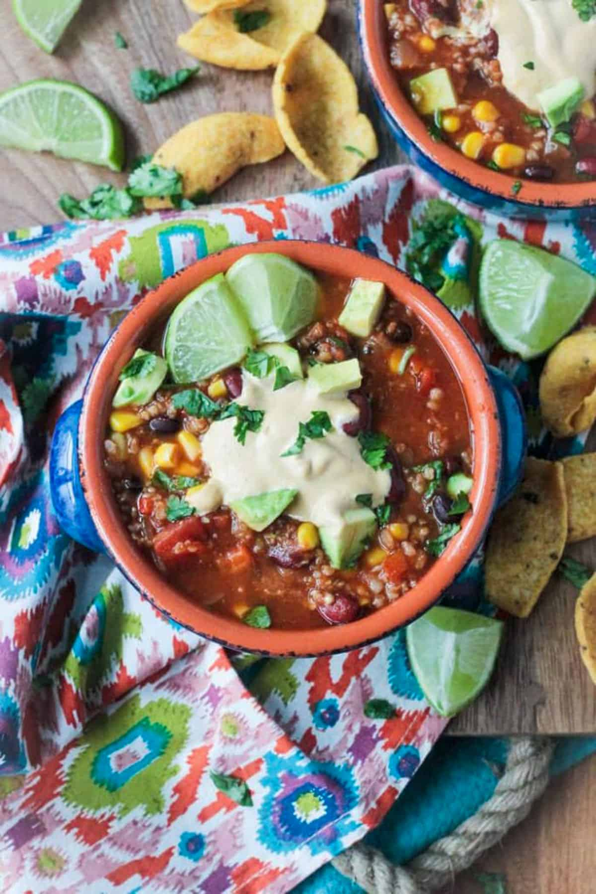 Taco Chili in a blue bowl topped with vegan ranch, cilantro, and lime wedges.