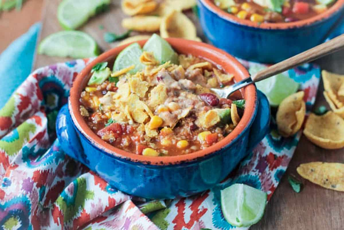 Crushed tortilla chips on top of a hearty bowl of chili.