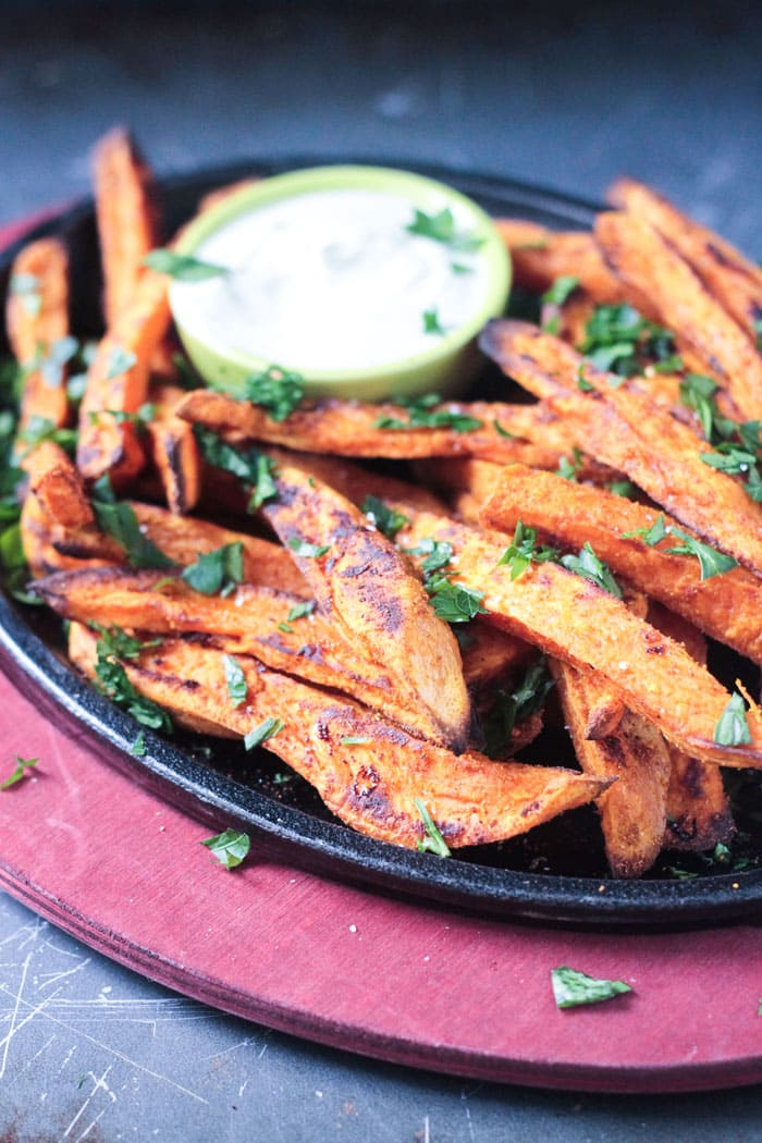 Side view of a plate of sweet potato fries sprinkled with parsley.