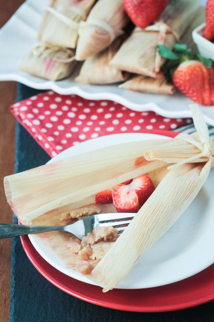 An unwrapped vegan strawberry dessert tamale on a plate. A fork taking a bite out of the filling. Fresh strawberries inside.