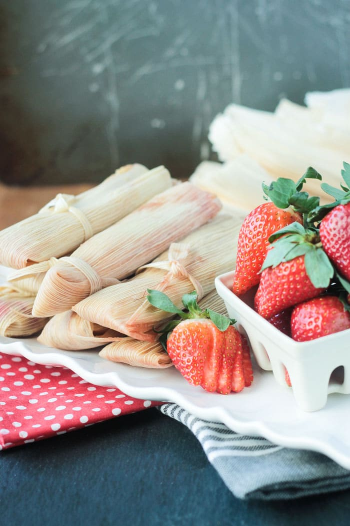 A plate of vegan tamales next to a white berry basket of fresh strawberries.