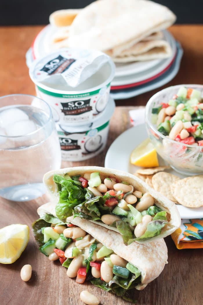 Two pita pockets filled with white bean salad stacked on top of each other. Glass of water, 2 stacked containers of yogurt, plate of pita bread, and a bowl of bean salad in the background.