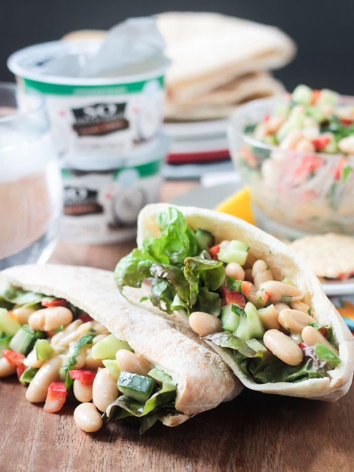 Two pitas filled with white bean salad and green leaf lettuce stacked on top of each other. Two yogurt containers in the background.