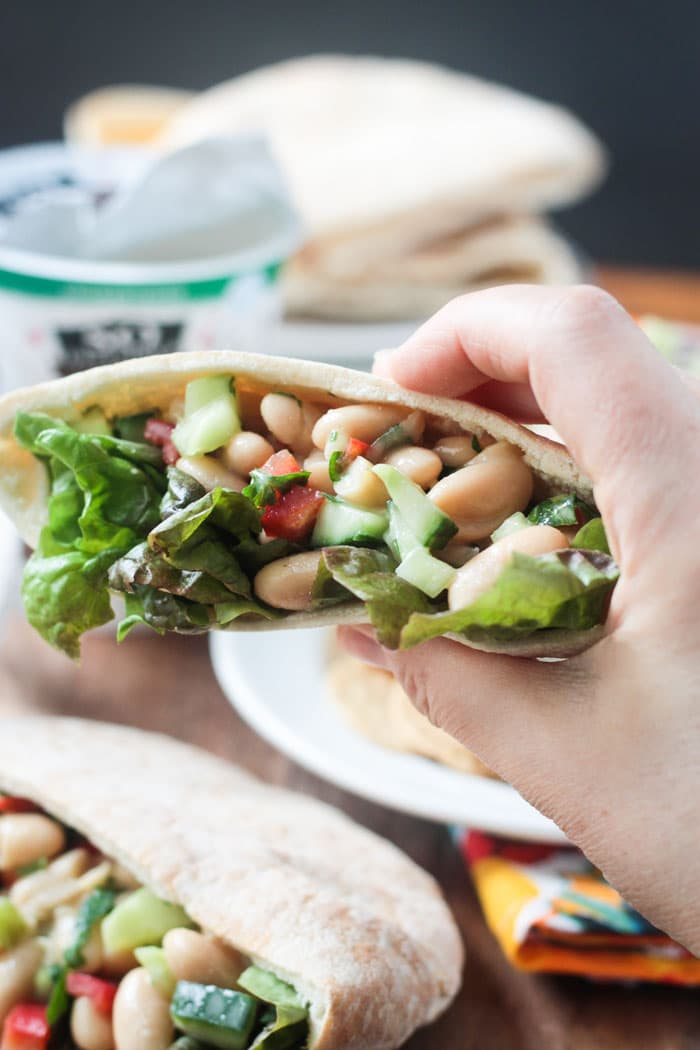 Hand holding a pita pocket filled with White Bean Salad.