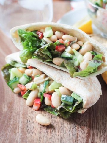 Two pita pockets stacked on top of each other and stuffed with White Bean Salad w/ cucumbers, red peppers, and red leaf lettuce.