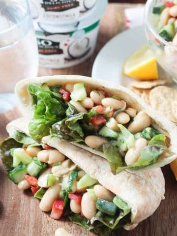 Two pita pockets filled with white bean salad stacked on a table.