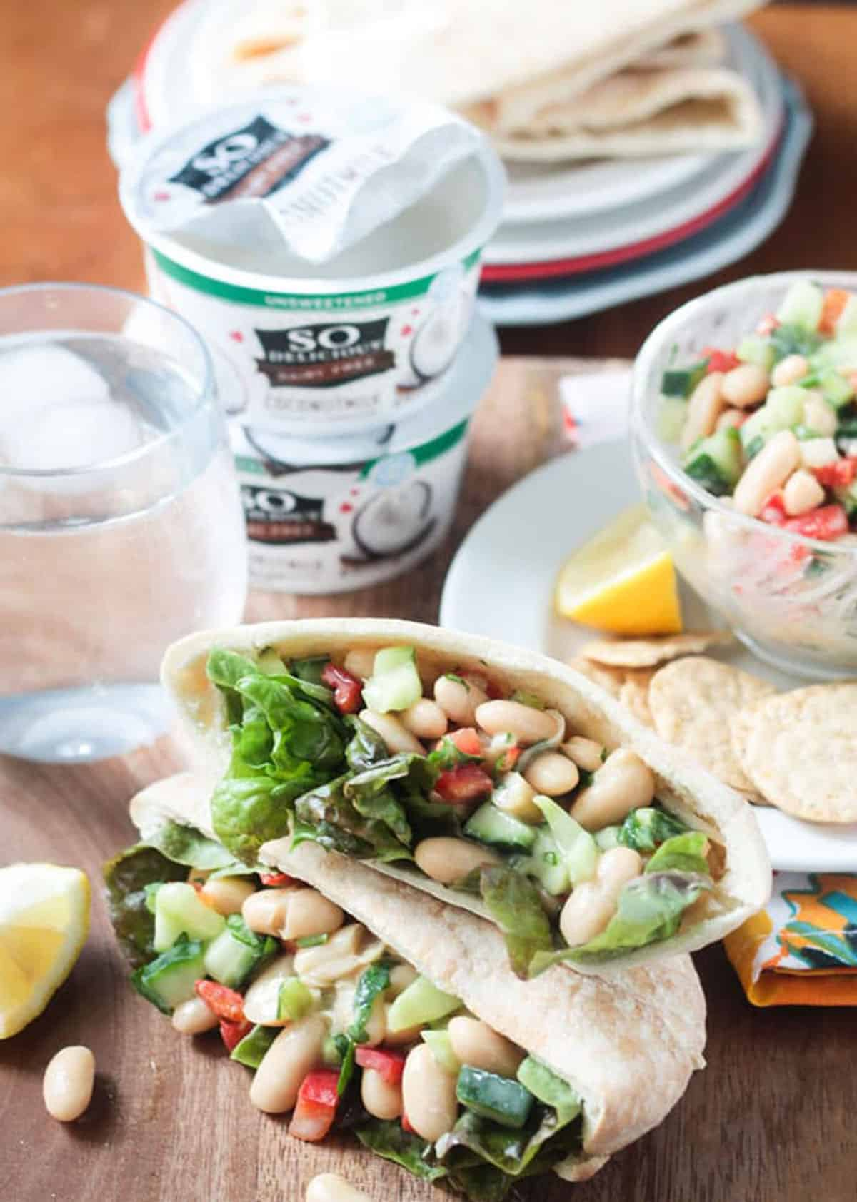 Two white bean salad pita pockets stacked in front of a yogurt container.