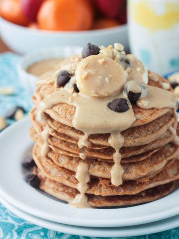 Stack of peanut butter pancakes topped with bananas, chocolate chips, and homemade maple peanut butter syrup dripping down the sides.