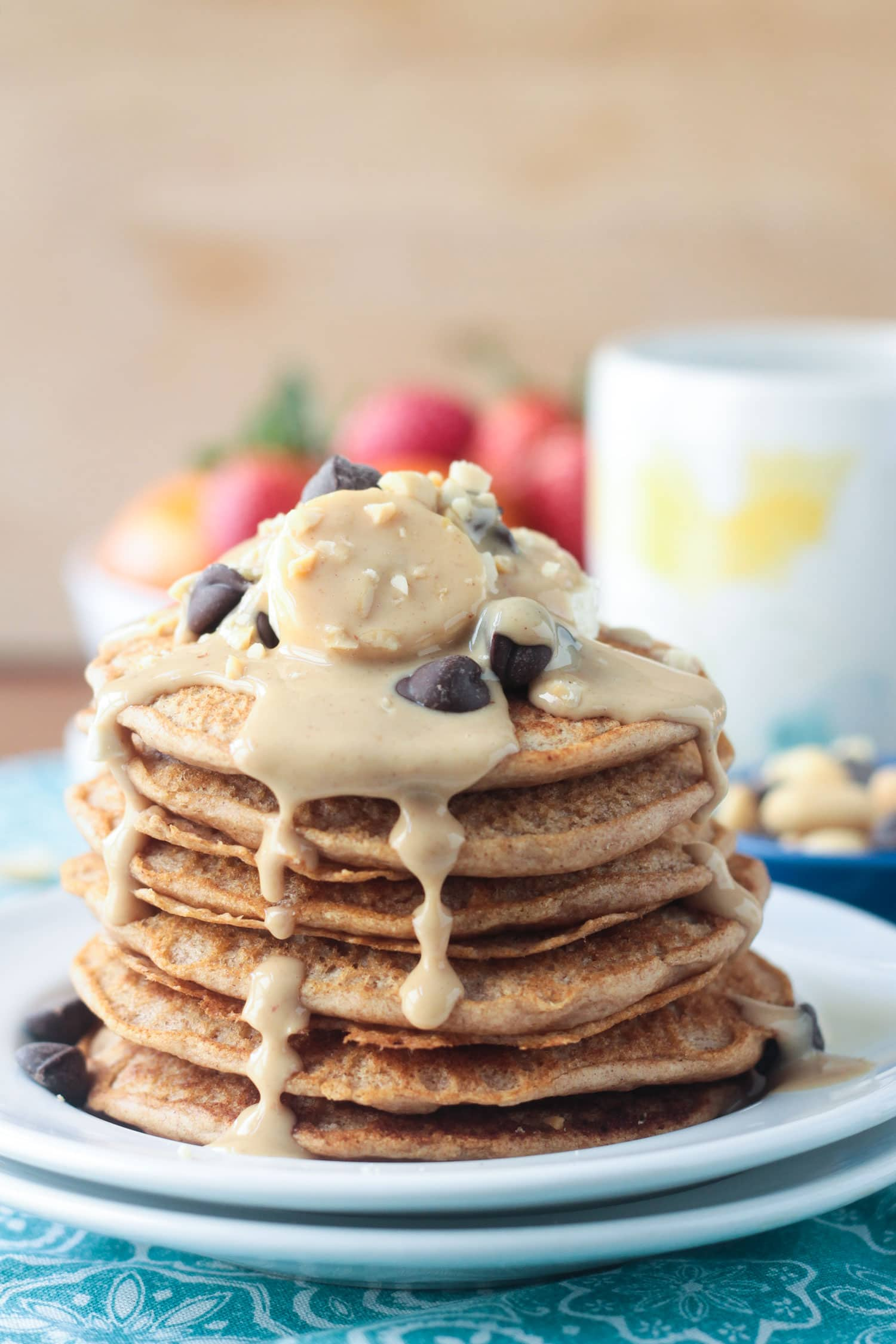 Stack of peanut butter pancakes drizzled in peanut butter syrup and topped with fresh banana slices and chocolate chips. A bowl of fresh oranges and berries and a coffee mug in the background.