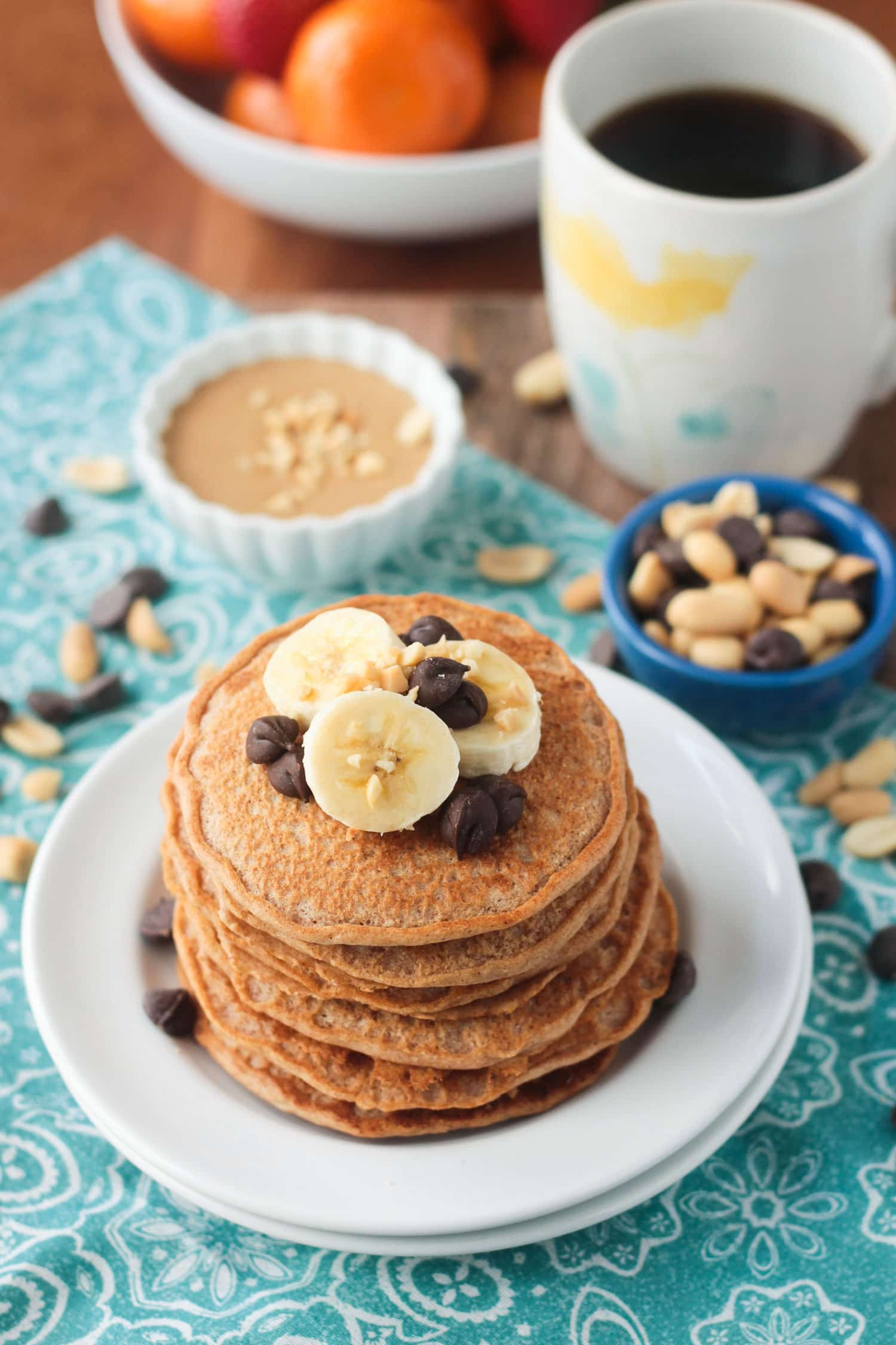 Stack of pancakes topped with banana slices and chocolate chips. Cup of coffee and a bowl of oranges in the background.