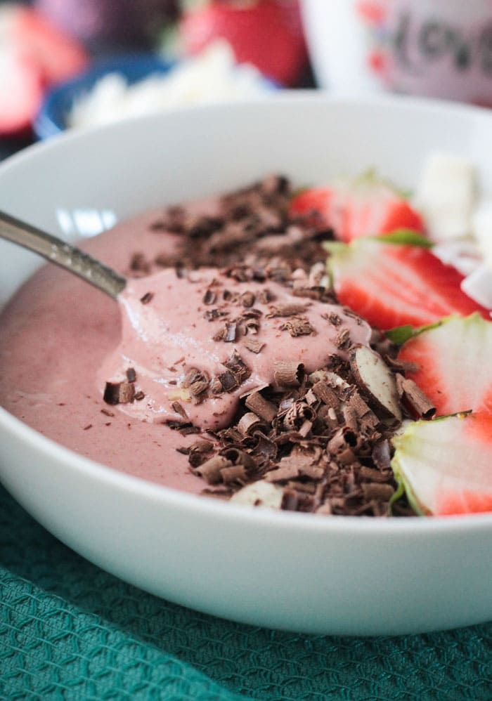 A spoon lifting out a scoop of Chocolate Covered Strawberry Smoothie Bowl.