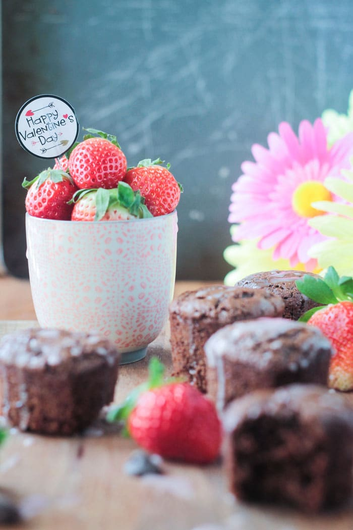 A small pink cup of fresh strawberries, with a Happy Valentine's Day cupcake topper sticking out of the top, surrounded by tahini chocolate chip cupcakes. Pink flowers in the background.