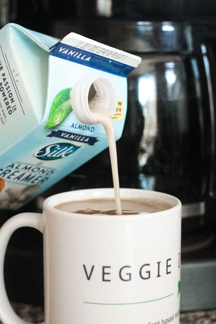 Silk Vanilla Almond Creamer being poured into a cup of coffee. Coffee pot in the background.