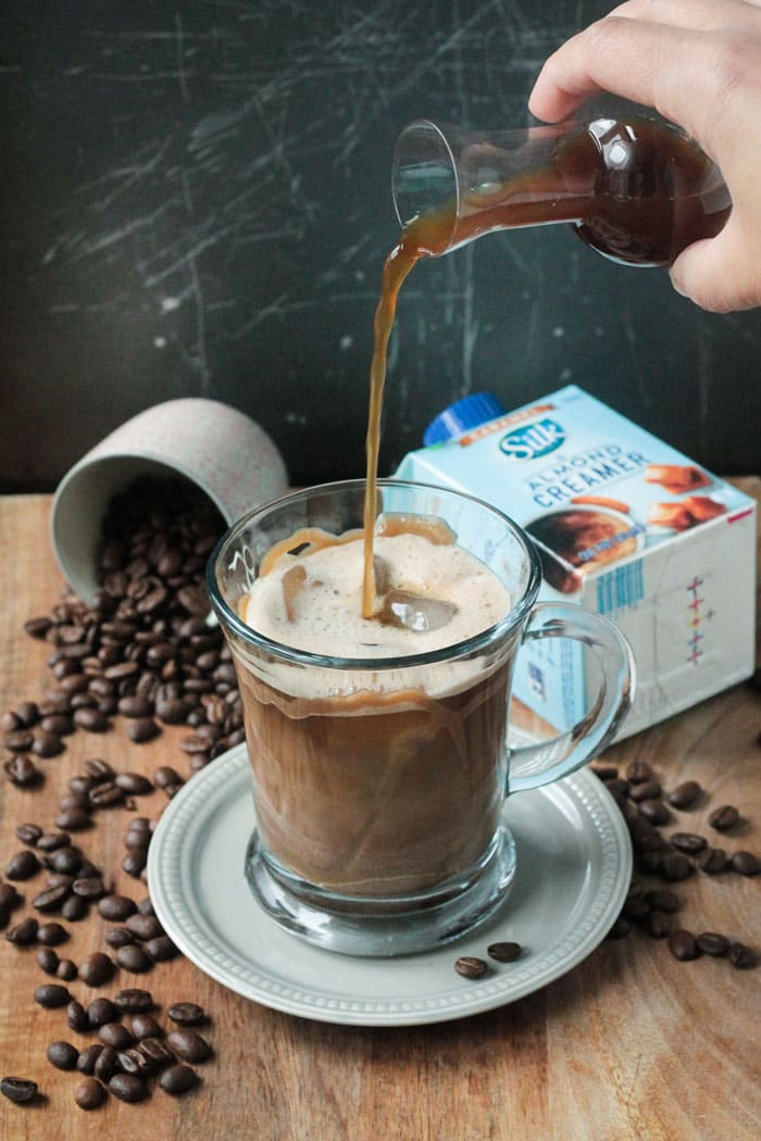 Coffee being poured from a small container into a glass coffee mug of homemade iced caramel macchiato. Container of Silk creamer in the background next to a spilled cup of coffee beans.