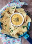 A small white bowl of Homemade Vegan Queso dip surrounded by a piles of tortilla chips sprinkled with cilantro.