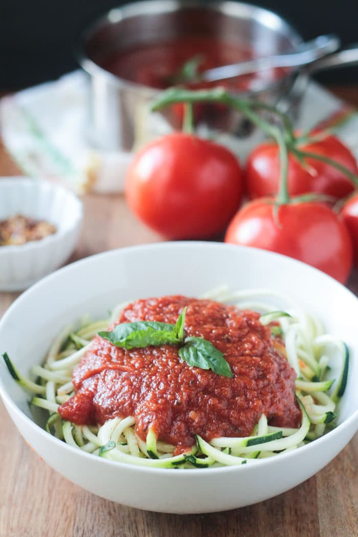A bowl of zucchini noodles topped with Spicy Marinara Sauce and fresh basil leaves. In the background, fresh tomatoes and the of marinara sauce.