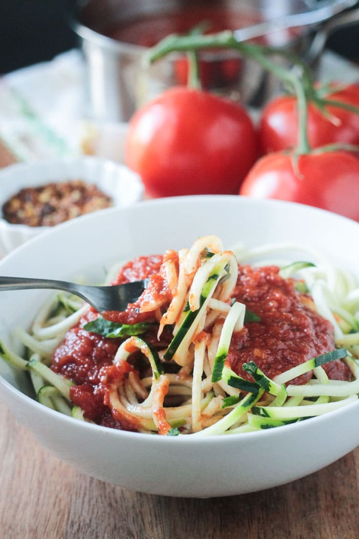 A bowl of zucchini noodles topped with Spicy Marinara Sauce. A fork is twirling the zoodles in the bowl. Fresh tomatoes, a tiny bowl of crushed red pepper flakes, and the pot of marinara sauce are in the background.