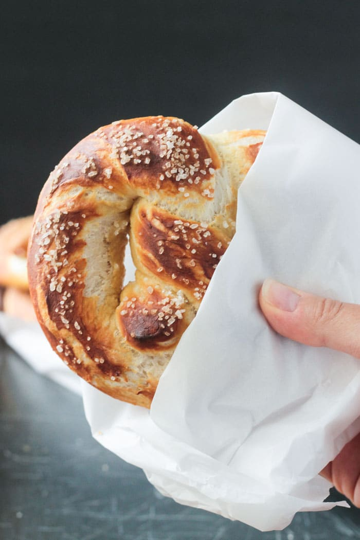 Hand holding a soft baked pretzel partially wrapped in a piece of parchment paper.