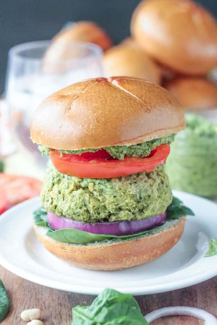 Spinach Artichoke White Bean Burgers with fresh spinach, red onion, tomato, and pesto on a wheat bun.