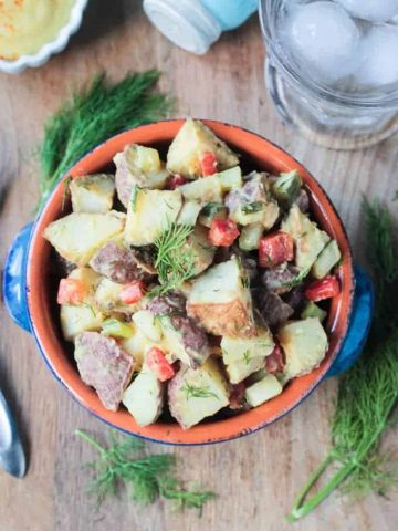 Overhead shot of roasted potato salad w/ red peppers, celery & pickles.