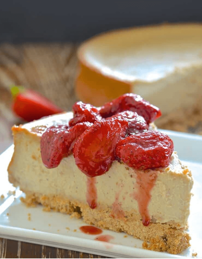 Slice of New York Cheesecake topped with roasted strawberries.