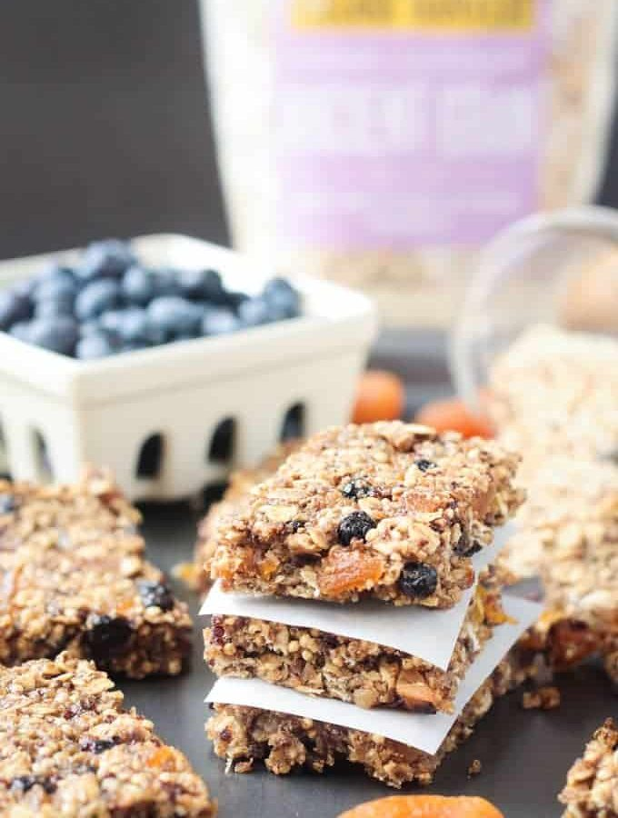 Stack of 3 Ancient Grains Breakfast Bars w/ parchment in between. Bowl of blueberries in the background.
