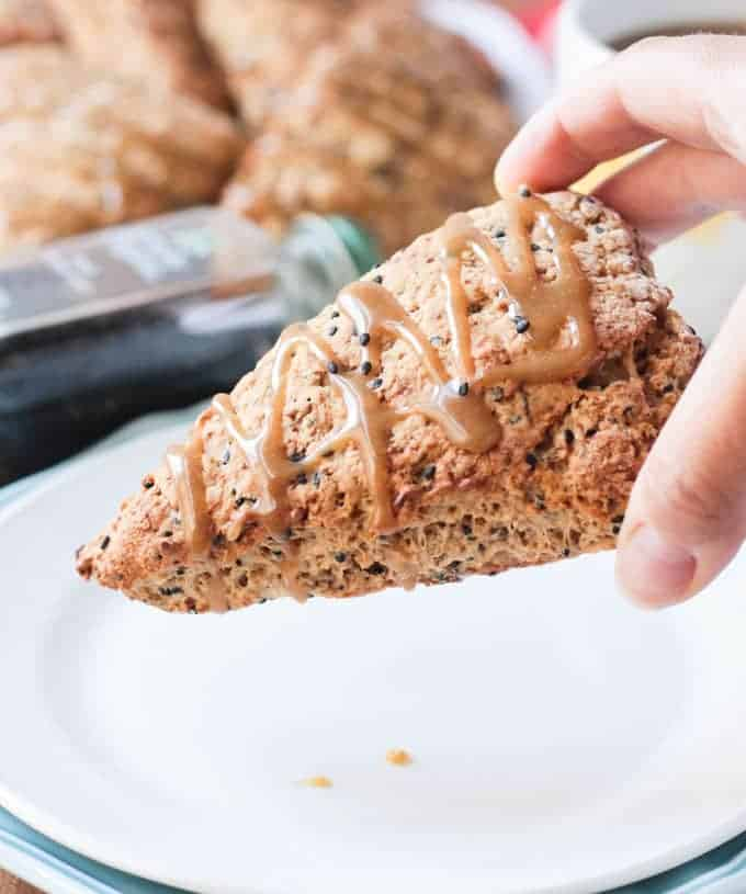 Hand holding a Banana Black Sesame Vegan Scones with Maple Tahini Glaze.