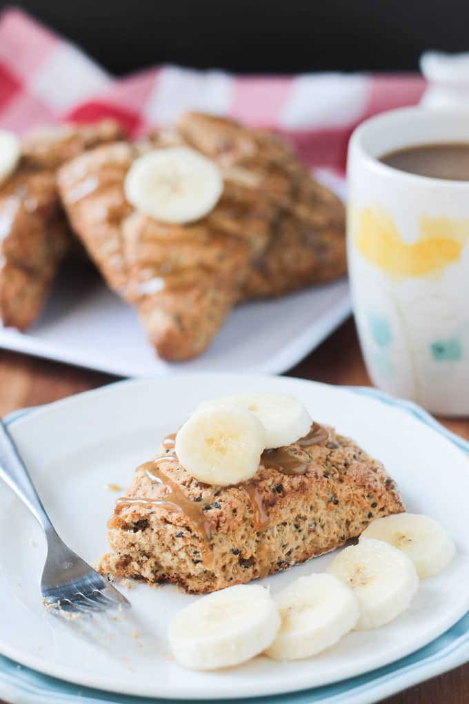 Banana Black Sesame Scone on a white plate topped with two slices of fresh banana. Metal fork lies across the plate along with more fresh banana slices.
