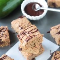 Stack of three chocolate chip zucchini bars, surrounded by more bars and a bowl of chocolate sauce in the background.