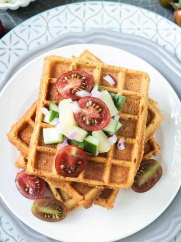 Crunchy corn waffles on a white plate topped with pineapple cucumber salsa and halved cherry tomatoes.
