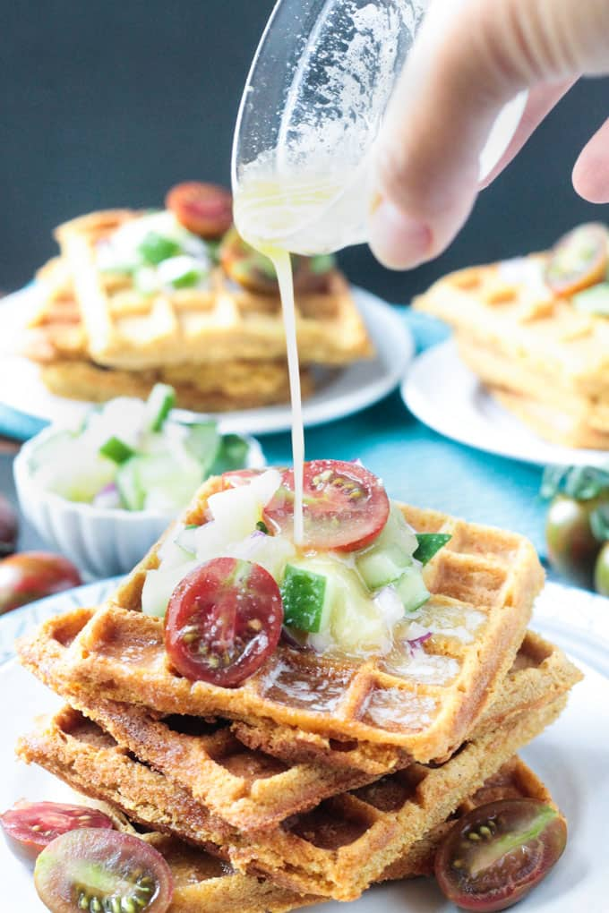 Drizzle of melted butter being poured over a stack of corn waffles garnished with halved cherry tomatoes and fresh pineapple salsa.