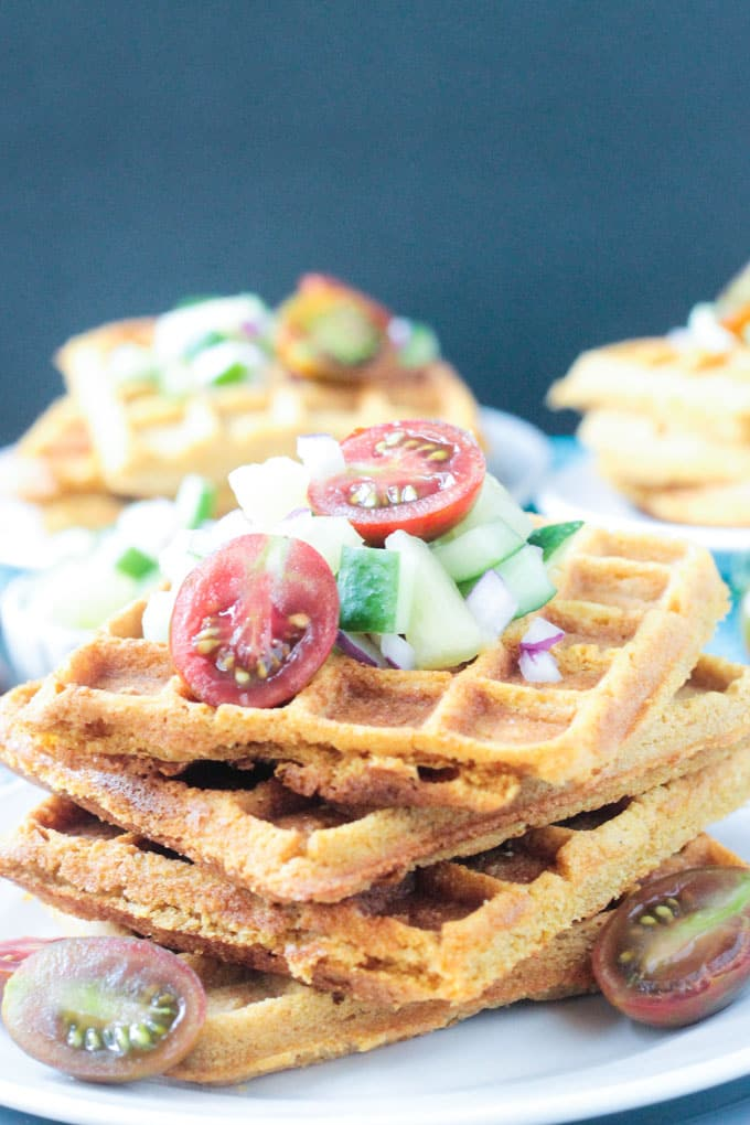 White plate stacked with cornmeal waffles and fresh pineapple cucumber salsa.