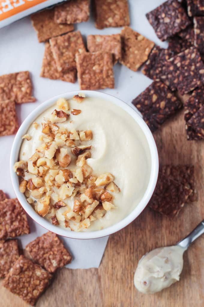 Overhead view of a bowl of cream cheese topped with chopped walnuts and surrounded by crackers.