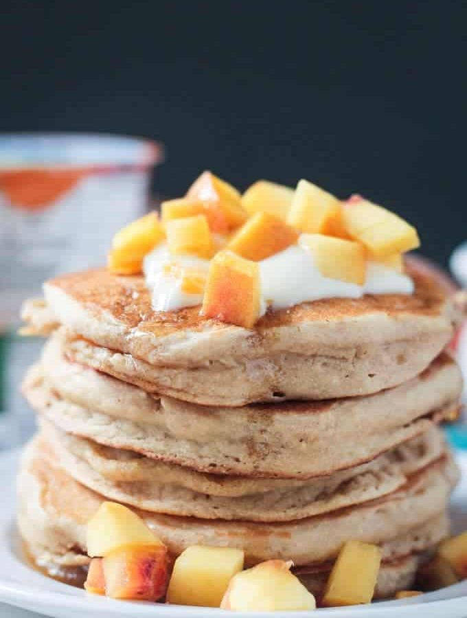 Close up photo of a stack of 5 peach pancakes.